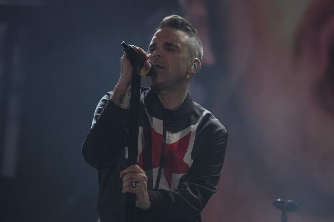 Robbie Williams rinde homenaje a su padre y llena al público de sorpresas