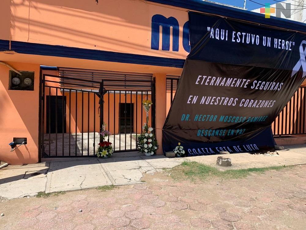 Afuera de clínica de Coatzacoalcos, colocan lona y arreglos florales en memoria del doctor Héctor Moscoso