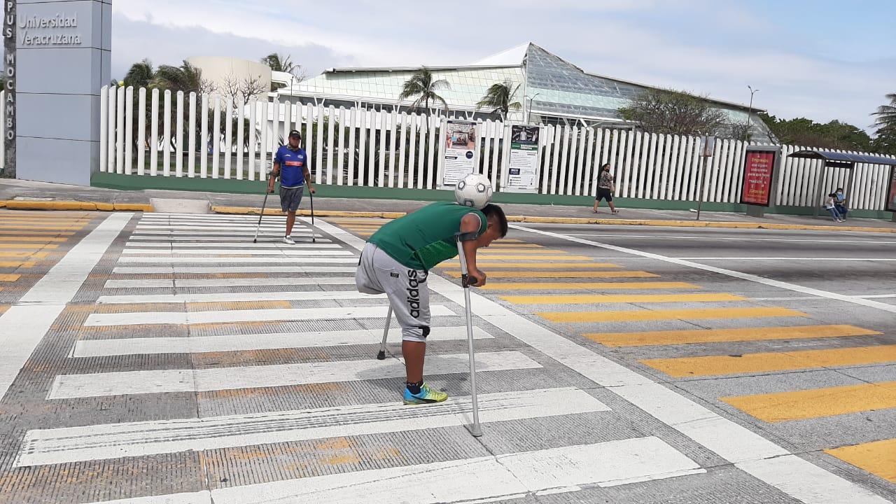 Amputados de sus piernas, dos jóvenes recorren el país dominando un balón de futbol para ganarse monedas